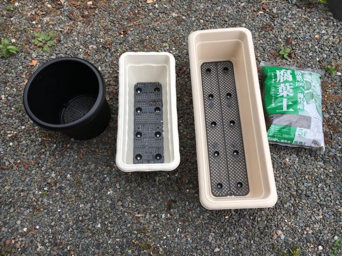 左からプラスチックの黒い鉢、長方形のプランターが2つ大と中、最後に腐葉土の入った袋