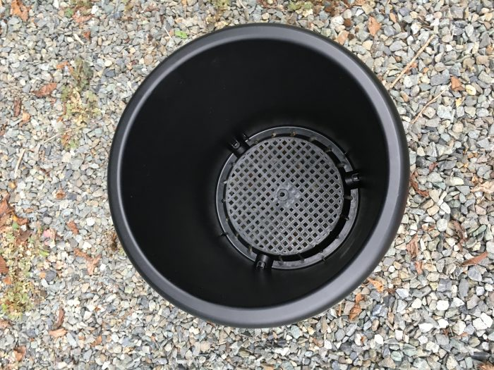 空のプラスチックの黒い鉢の底が網になっている
